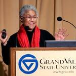 Patricia Hill Collins presenting behind a podium with the Grand valley state logo present
